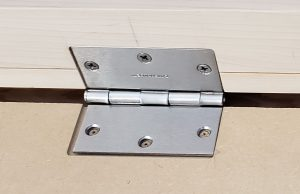 Close up of installing a hinge.